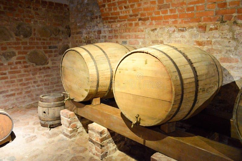 Barriles de madera de la ronda grande para la cerveza, vino en el sótano viejo de las Edades Medias hechas de ladrillo fotografía de archivo
