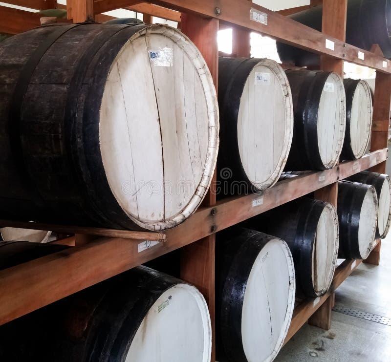 Barriles de madera negros grandes para el almacenamiento de las bebidas agrupadas en un estante del sótano fotografía de archivo