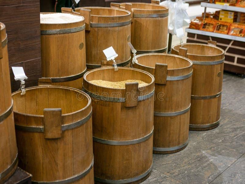 Barriles de madera viejos con maíz, arroz y alforfón en mercado fotos de archivo libres de regalías