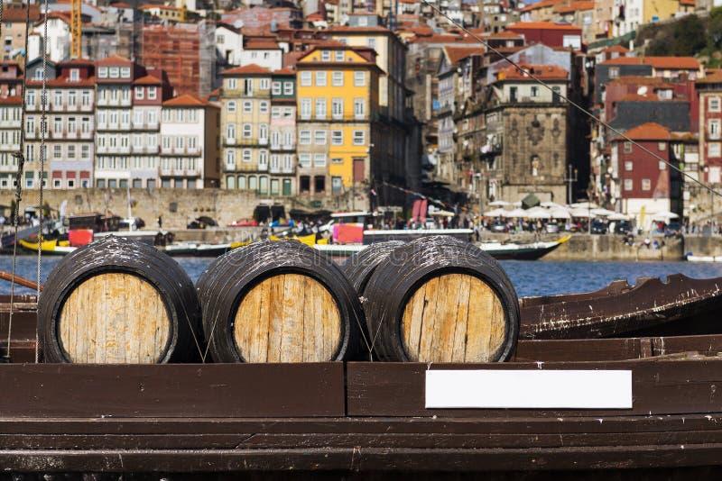Barriles de vino de Oporto en un barco en el río del Duero con la ciudad de Oporto en el fondo imagen de archivo libre de regalías