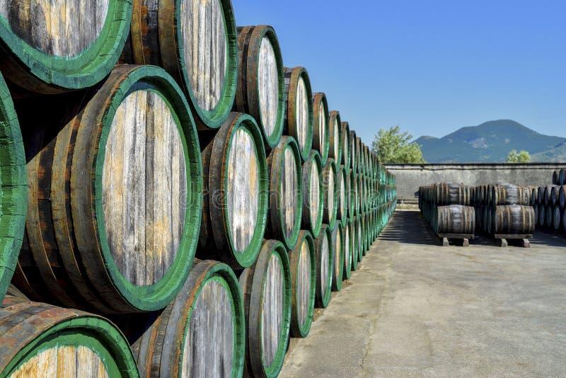 Barriles de vino de madera viejos apilados en aire abierto foto de archivo