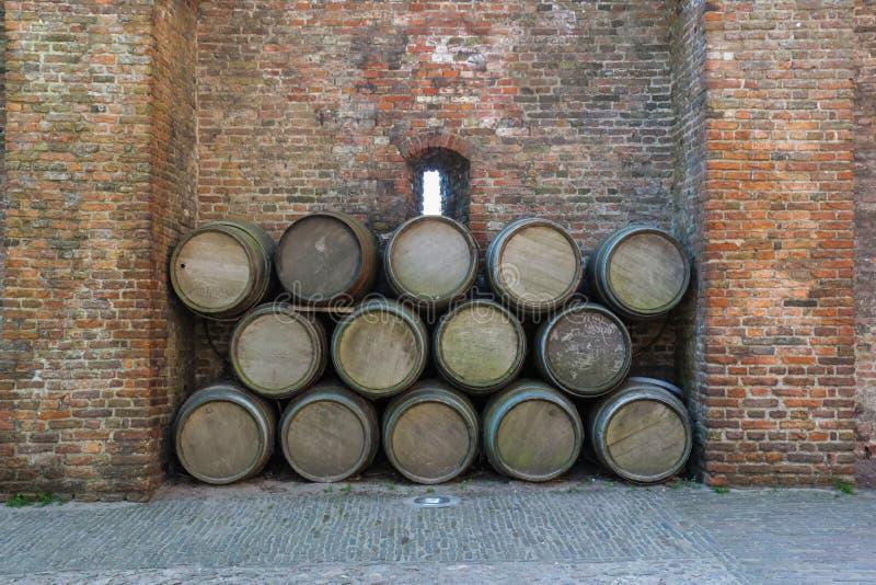 Barriles de vino viejos apilados contra una pared de ladrillo rústica fotos de archivo