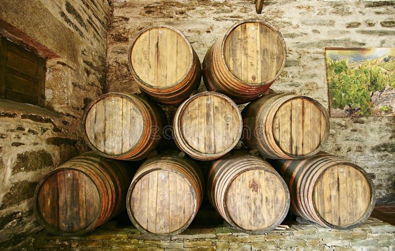 Barriles grandes de vino de Oporto apilados contra la pared foto de archivo