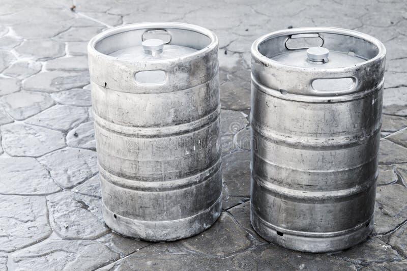 Barriletes de aluminio usados, pequeños barriles con la cerveza imagenes de archivo