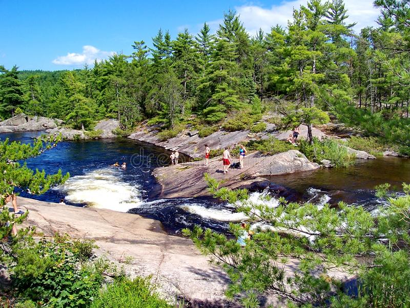 People play and swim at the natural water slide located on the Barron River royalty free stock photography