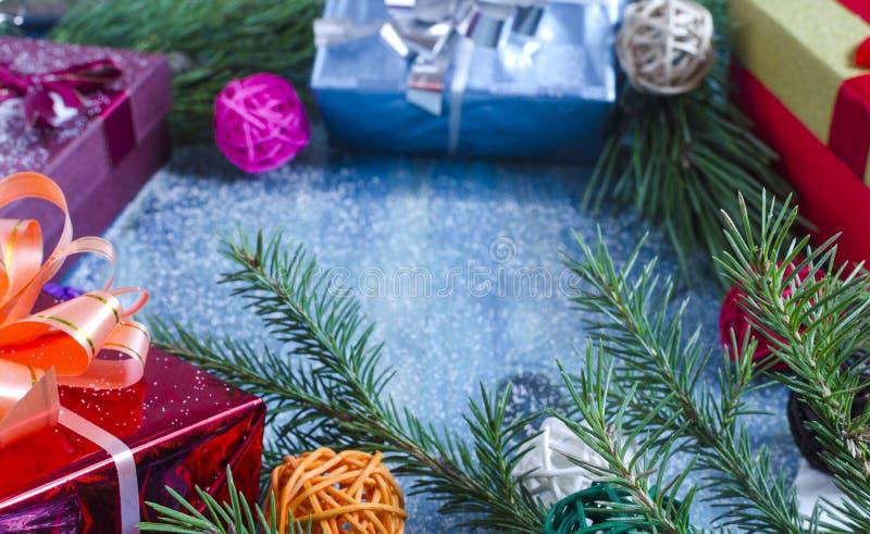 Barrträds- filialer för gåvaaskar på den blåa closeupen för utrymme för kopia för nytt år för bakgrund royaltyfri bild
