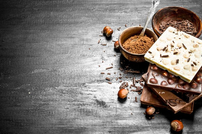 Bars of different types of chocolate with cocoa powder. royalty free stock photos