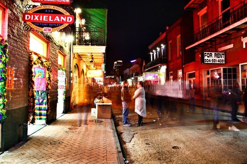 Bars en bars met neonlichten, zijdelings portret van een gelukkig paar die bij elkaar in Frans Kwart staren stock foto