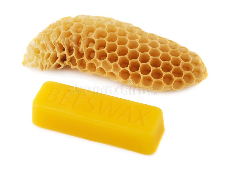 A bar of natural beeswax and a piece of bee honey on a white background. Beekeeping products. Apitherapy stock photography