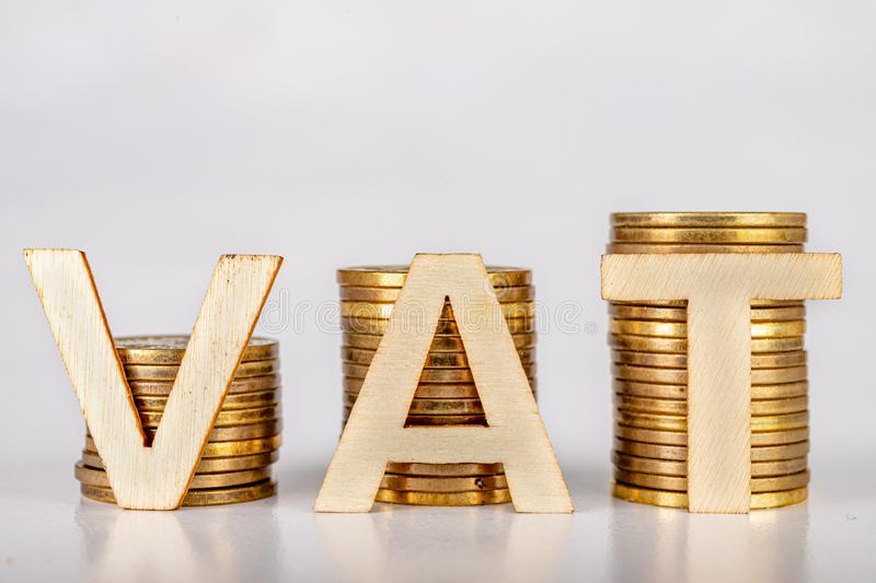 Bars stacked from coins on a white table. VAT inscription with wooden letters based on coins royalty free stock images