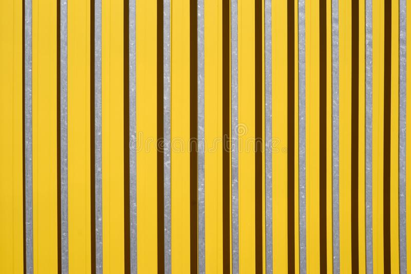 Bars throw shadows. The side view of a color-intensive corrugated iron wall of a shopping center with bars in front of the wall royalty free stock photography