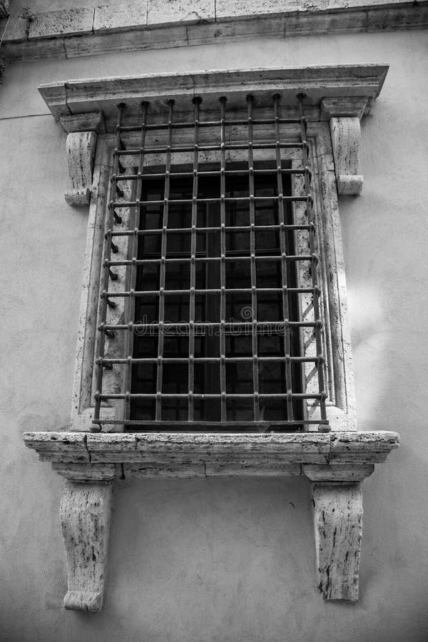 Bars on the window. Inglese Italiano Old window with bars stock photos