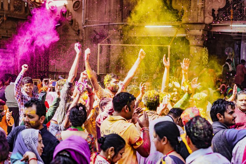 Barsana, India / February 23, 2018 - The crowd erupts in laughter and dance as powdered paint thrown in the air during Holi royalty free stock images