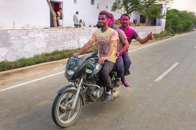 Three unidentified indian men riding one bike covered with powdered dyes during for Holi festival in India royalty free stock photos