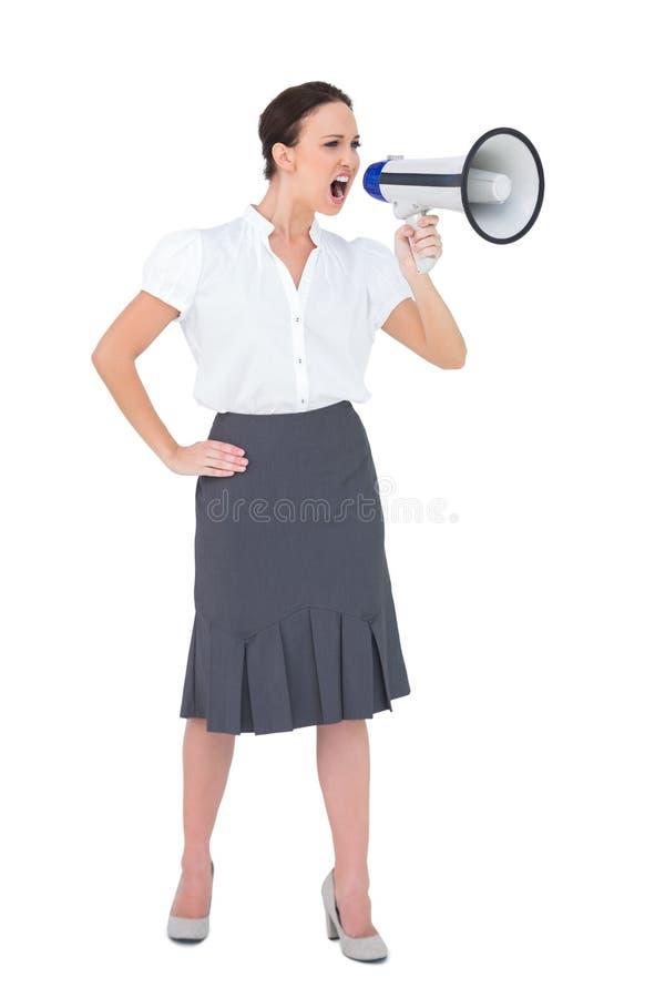 Barsk affärskvinna som ropar i hennes megafon arkivfoto