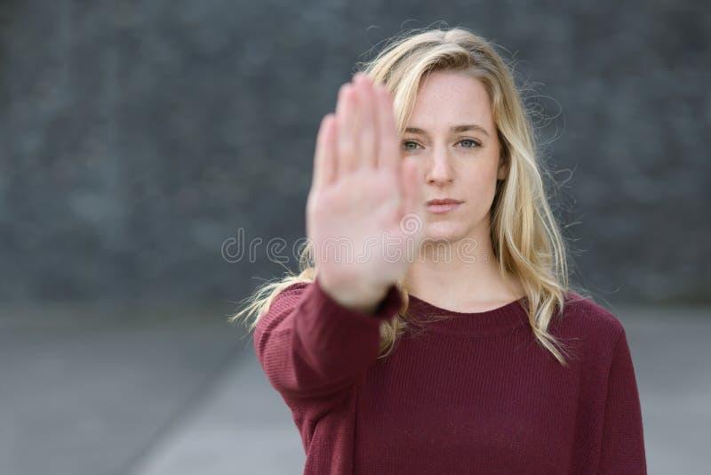 Barsk ung kvinna som gör ett stopp att göra en gest fotografering för bildbyråer