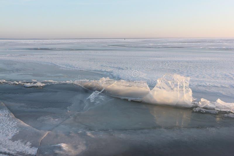 Barsten met ijskristallen op bevroren rivier bij zonsondergang stock afbeelding