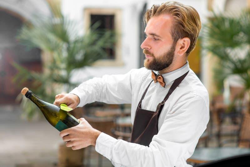 Bartenderöppningsflaska med mousserande vin royaltyfri bild