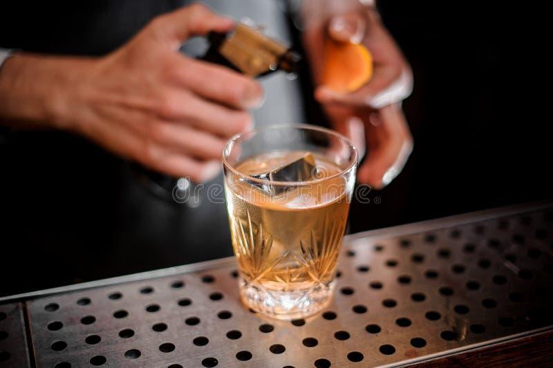 Bartender έτοιμο να βάλει φωτιά σε μια πορτοκαλιά απόλαυση και προσθήκη του στον οινοπνευματώδη χυμό στοκ φωτογραφία