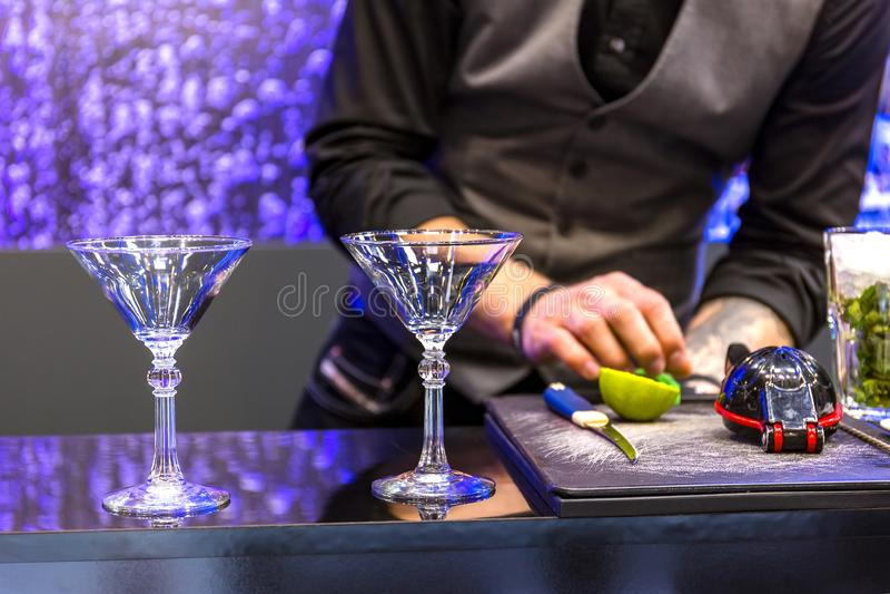 Bartender βάζει το φρέσκο ασβέστη στην υαλουργία το κοκτέιλ r στοκ φωτογραφία