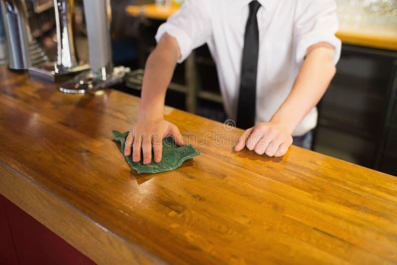 Bartender καθαρίζοντας μετρητής φραγμών στοκ φωτογραφίες