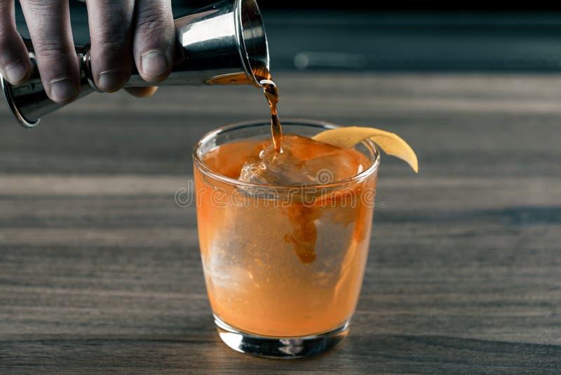 Bartender μπάρμαν με το κοκτέιλ που προετοιμάζουν το πορτοκαλί κοκτέιλ στο φραγμό Ποτά οινοπνεύματος στοκ εικόνες