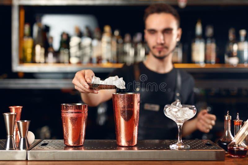 Bartender που κατασκευάζει το κοκτέιλ Μπάρμαν που βάζει τον πάγο στο γυαλί στοκ φωτογραφία
