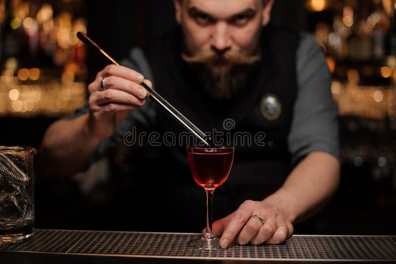 Bartender που προσθέτει ένα ντεκόρ με τα τσιμπιδάκια στο γυαλί στοκ εικόνες με δικαίωμα ελεύθερης χρήσης
