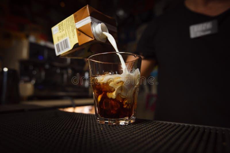 Bartender χύνει την κρέμα σε ένα κοκτέιλ στοκ εικόνες
