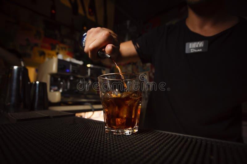 Bartender χύνοντας οινόπνευμα σε ένα γυαλί στοκ φωτογραφία