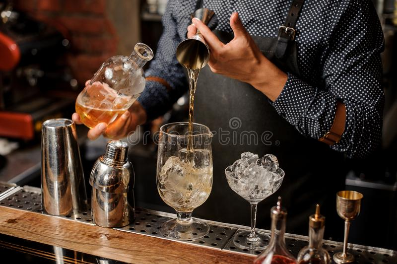 Bartender adding a portion of syrup into the large cocktail glass. With ice cubes on the bar counter royalty free stock photography