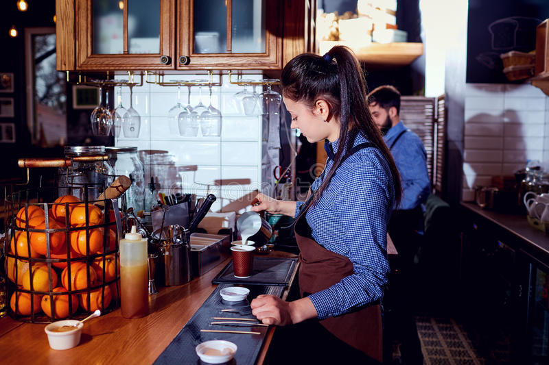 The bartender barista girl makes hot milk at the bar in cafe res stock images