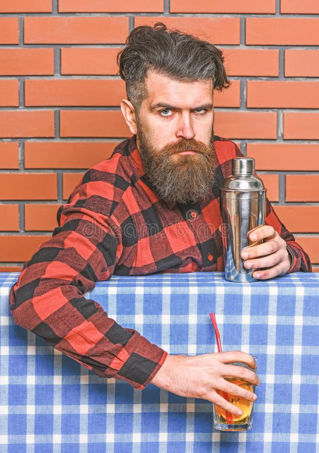 Bartender concept. Barman with long beard and mustache and stylish hair on strict face holding shaker, made alcoholic. Cocktail. Man in checkered shirt on brick stock images