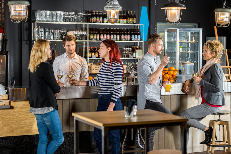 Bartender With Customers Having Drinks In Bar. Young bartender with customers talking and having drinks in bar royalty free stock image