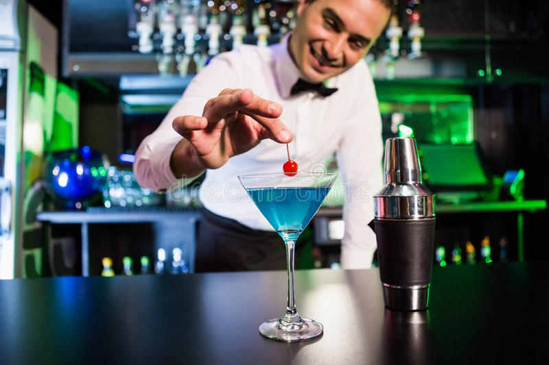 Bartender garnishing cocktail with cherry royalty free stock images