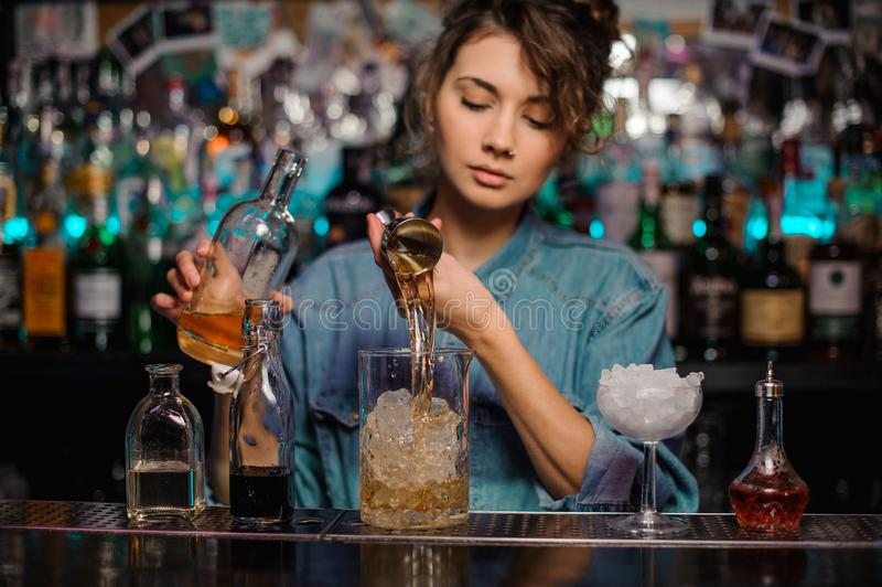 Bartender girl pouring to the measuring glass cup with ice cubes an alcoholic drink from jigger. On the bar counter on the blurred background stock photo