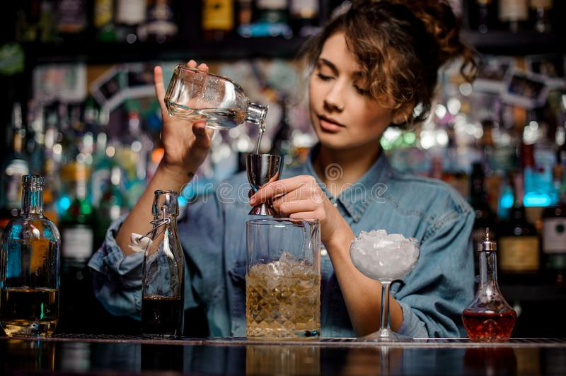 Bartender girl pouring to the steel jigger an alcoholic drink on the bar counter stock images