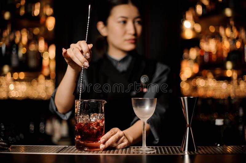 Bartender girl stirring a delicious cocktail with a steel spoon in the measuring glass cup. On the bar counter in the dark blurred background royalty free stock photo