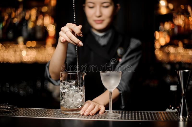Bartender girl stirring an ice cubes with a steel spoon in the measuring glass cup. On the bar counter in the dark blurred background royalty free stock photos