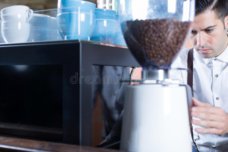 Bartender grinds coffee beans stock photo