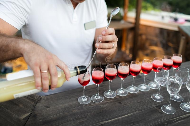 Bartender hands pouring alcohol in red cocktail. Bartender hands pouring alcohol into the cocktail glasses filled with red beverage. Evening party, wedding royalty free stock images