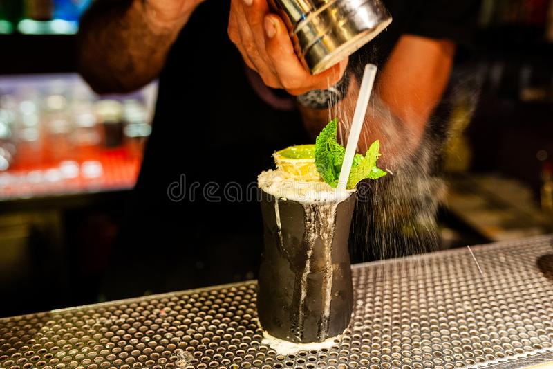 Bartender hands pouring icing sugar on lost lake cocktail  with mean leaves inside night cocktail bar. Close up stock photo