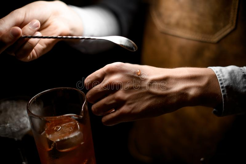 Bartender holding a spoon and put a drop on the hand. On the bar counter in the dark blurred background stock image