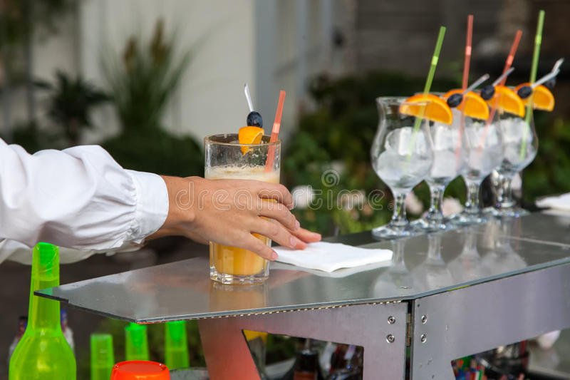 Bartender holds glass of cocktail stock photo