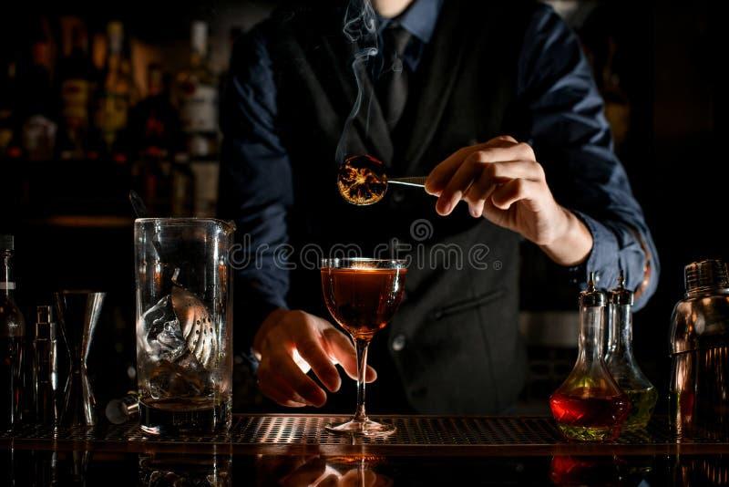 Bartender houdt een pincet met een stukje citrus boven glas drank royalty-vrije stock afbeelding
