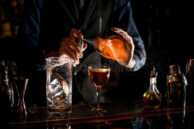 Bartender houdt een pincet met een stukje citrus over de sproeiers van glas vast en zet het in brand royalty-vrije stock afbeeldingen