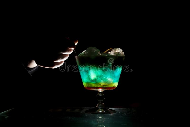 Bartender makes a multi-colored cocktail with ice and foam in a glass on a black background, hands hold the drink royalty free stock image
