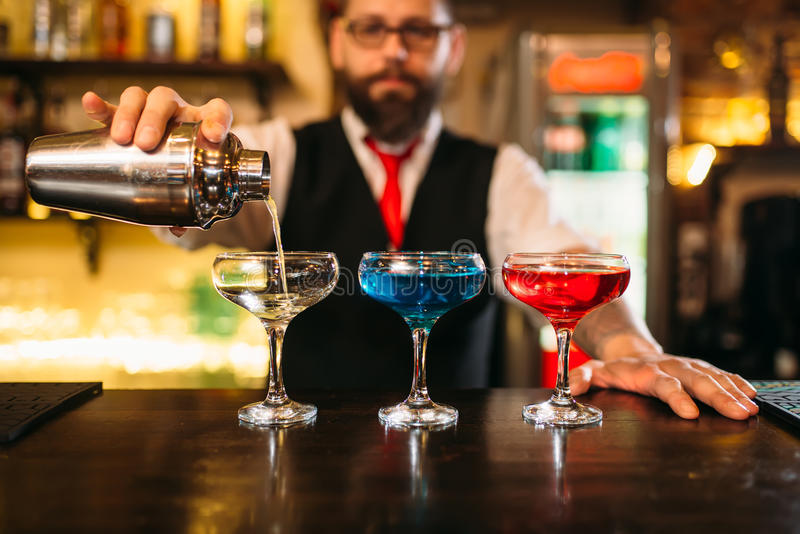 Bartender making alcohol beverages in nightclub. Bartender with shaker making alcohol beverages behind a bar counter in nightclub royalty free stock photo