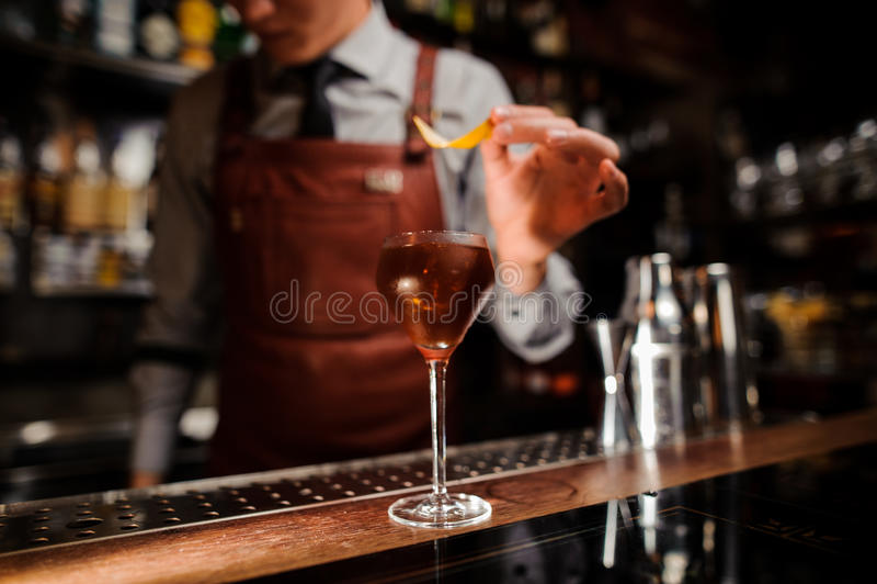 Bartender med exponeringsglas och citronskal som förbereder coctailen på stången arkivbilder
