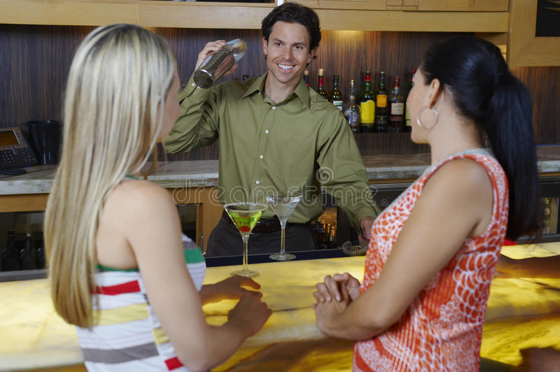 Bartender Mixing Drinks For Women At Bar stock photography
